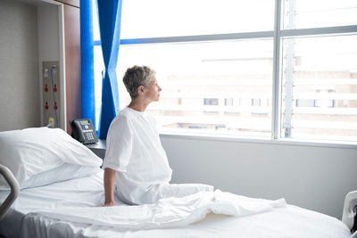 Is autumn the time for patients to plan cosmetic procedures? - Image showing a woman in a hospital gown on a hospital bed looking out the window