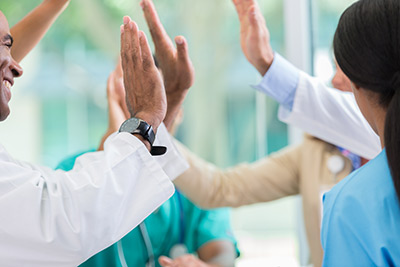 Is there a place for cosmetic surgery on the NHS? - Image of excited medical professionals giving high fives