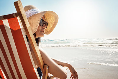 The best advice for preventing sun damage - Image of a women relaxing on a chair at the beach