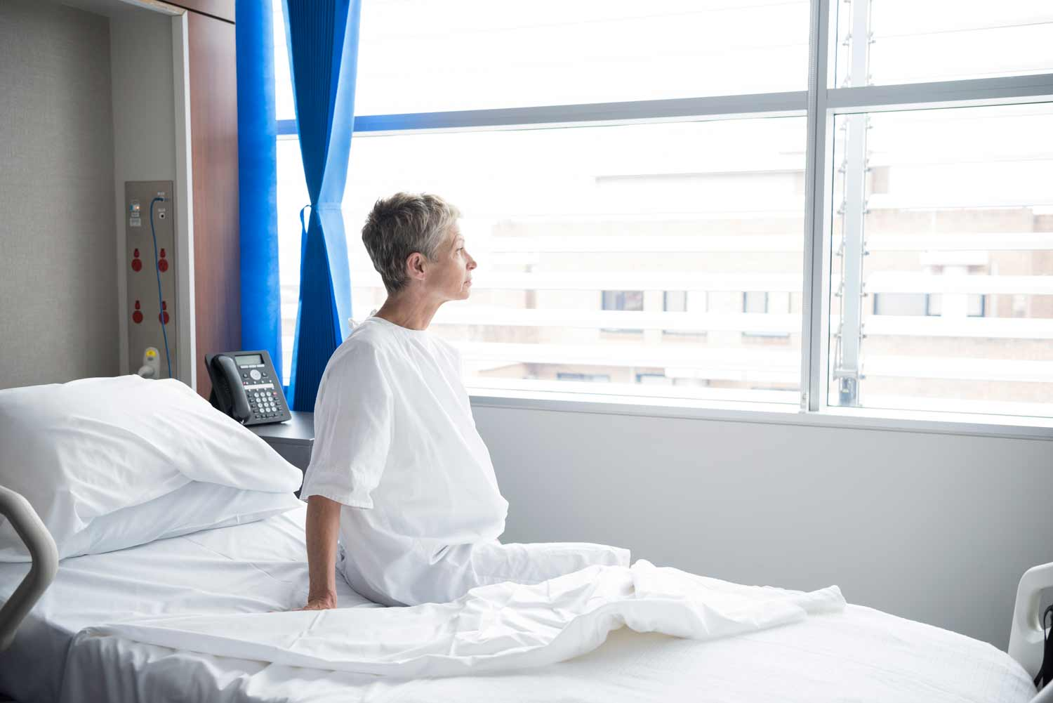 When is the best time to plan cosmetic procedures? - Image showing a woman sitting in a hospital bed looking out of the window