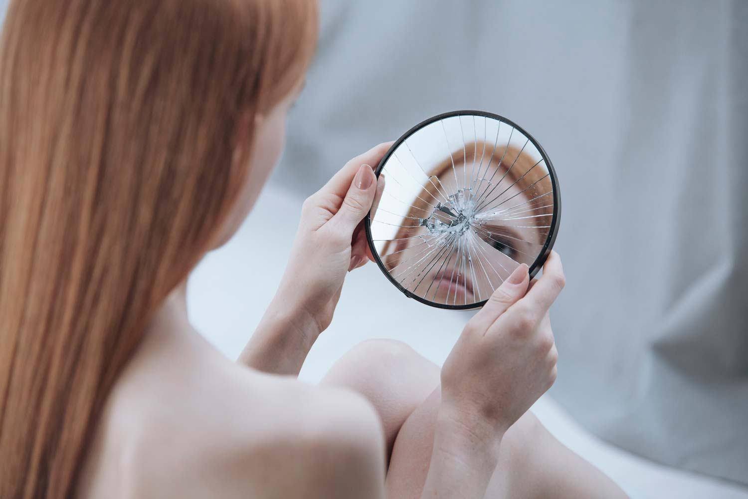 Body Dysmorphic Disorder in aesthetics: the role of the practitioner - Image showing the distorted reflection of a women in a small mirror